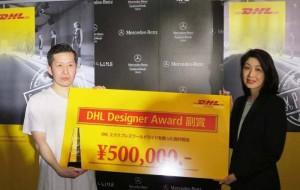 DHL ジャパン セールス&マーケティング本部 マーケティングコミュニケーションズマネージャーの髙田淳子よりDHL デザイナーアワードを受け取る末安 弘明氏